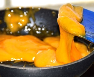 Melted cheese in a pan for topping a burger.