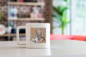 Square shaped mug with a picture of a baby on it.