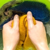 Hands washing a yellow sweater by hand.