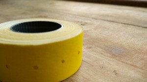 Roll of tape on a piece of wood.
