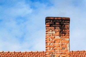 Brick chimney with black soot on the top.