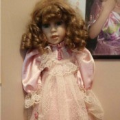 Identifying a Porcelain Doll - doll with reddish ringlets and wearing a pink dress