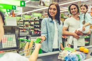 Family paying for groceries at supermarket