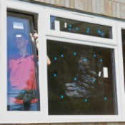 Man installing new windows with labels on them