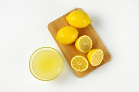 Cut lemons on a cutting board with lemon juice in a glass bowl