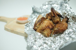 Baked chicken in aluminum foil on wooden cutting board