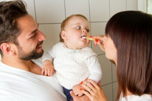 Couple brushing their baby's teeth
