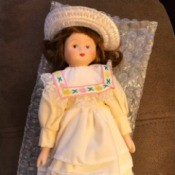Porcelain Doll Identification - small porcelain doll wearing a straw hat