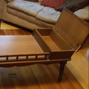 Value of a Mersman Coffee Table - medium wood finish table with covered end compartments and railing between