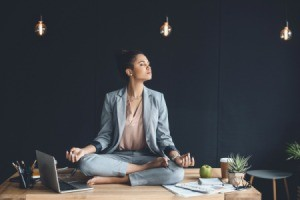 Woman meditating on her work desk.