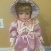 Value of Heritage Porcelain Dolls - doll wearing a pink satin and lace dress