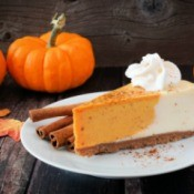 Pumpkin cheesecake with cinnamon and small sugar pumpkins on the side