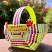 Craft Paper Basket - basket sitting outside on deck railing