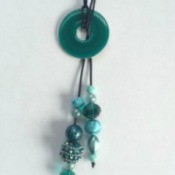 A lariat necklace with a decorated washer in the middle.