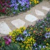Gravel garden path with colorful flowers on each side.