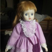 Identifying a Porcelain Doll - red haired doll wearing a purplish pink dress