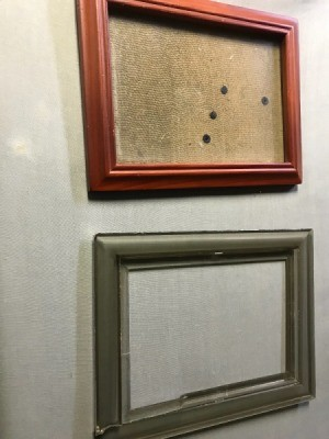 A broken picture frame underneath another frame that has had the glass replaced.