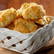 Garlic cheese biscuits in a white ceramic basket.
