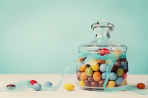 Glass jar filled with colorful candy, tied with a bow.
