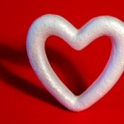 Styrofoam heart wreath on a red background.