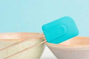 Blue rubber spatula on the edge of a bowl