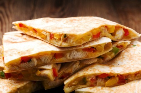 Pan Fried Chicken Quesadilla slices stacked on a plate