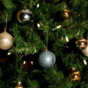 Close up of Christmas tree with lights and gold and silver baubles.