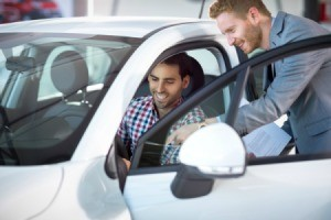 Man looking at rental car with sales person