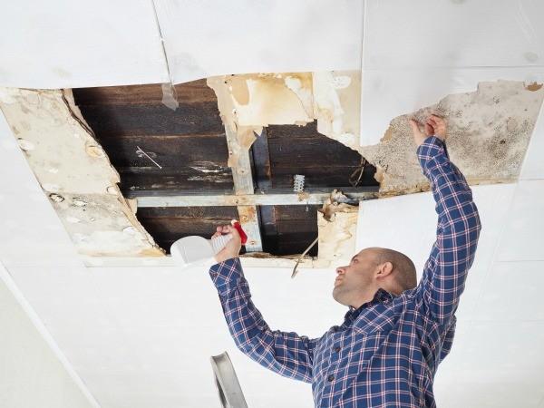 Man Repairing Ceiling That Has A Hole