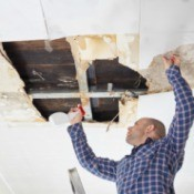 Man repairing ceiling that has a hole
