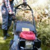 Man pulling start cord on lawn mower