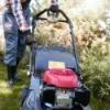 Man pulling start cord on lawn mower