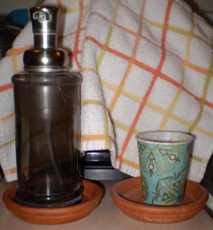 A soap dispenser and a water glass inside terra cotta planter bases.