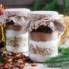 Jars filled with brownie mix in layers topped with burlap.