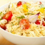 Orzo in a bowl with tomatoes and shallots.