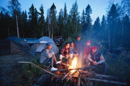 Family out camping siting around fire at dusk