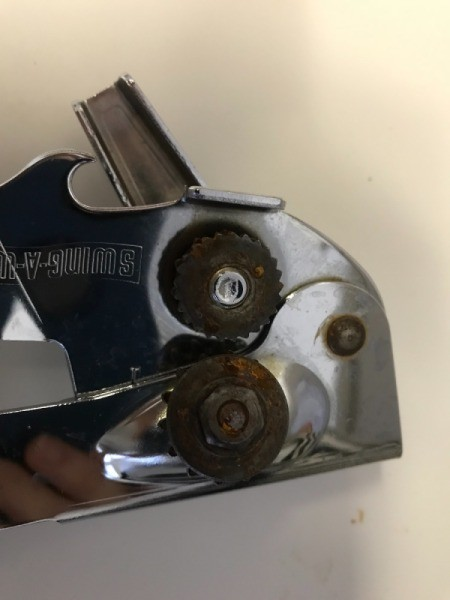 A can opener that has rust on the cutting blades.