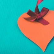 Orange paper heart with a red ribbon, on a aqua colored cardstock.