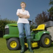 Woman standing next to a riding lawn mower.
