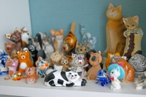 Wooden and porcelain figurines of cats from different cities and countries.