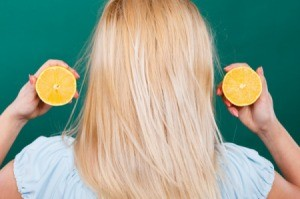 Back of a blonde haired person holding up a cut lemon next to their hair.