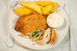 Chicken Kiev on a plate with fries.