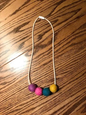 Toddler Felt Ball Necklace - finished necklace on a table top