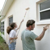 Father and daughter painting the exterior of their house.