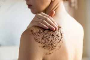 Woman Exfoliating her shoulder with coffee grounds