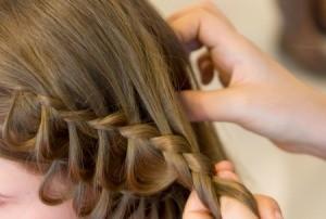 Woman braiding a girls hair