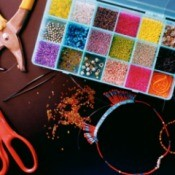 Organized craft beads with scissors on a wooden table