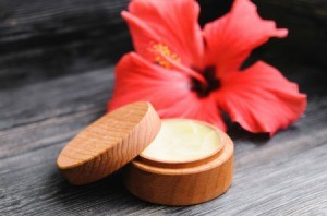 A wooden jar filled with lip balm and a pink flower on a wooden background.