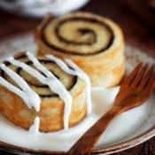 Two small cinnamon rolls on a tea saucer.