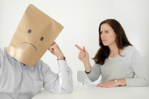 Abusive wife pointing at a man with a paper bag on his head with a sad face.